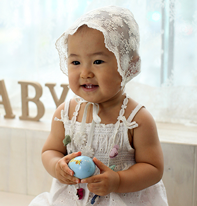 흰색 모자를 쓰고 흰색 원피스를 입은 여자아이가 손에 장난감을 들고 앉아 있다