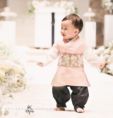 한복을 입은 남자 아이가 꽃이 장식 된 실내에서 앞으로 걸어 오고 있다