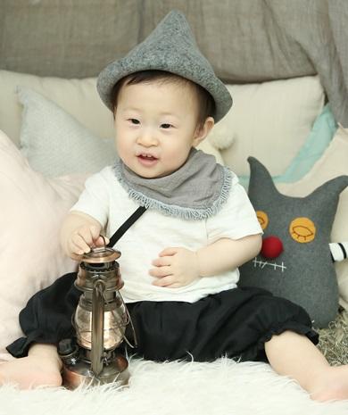 회색모자를 쓰고 흰색 반팔과 검정색 바지를 입고 회색 스카프를 한 남자아이가 러그 위에 앉아서 앞에 놓인 램프를 오른손으로 잡고 있다