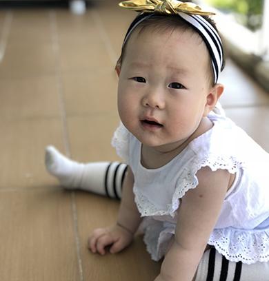 머리띠를 한 여자아이가 흰색 원피스를 입고 바닥에 앉아 정면을 보고 있다