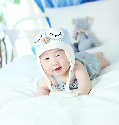 하늘색 옷을 입고 하얀 침대에 누워있는 아이