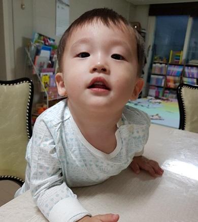 남자아이가 테이블에 손을 집고 턱을 들어 올리며 정면을 바라보고 있다