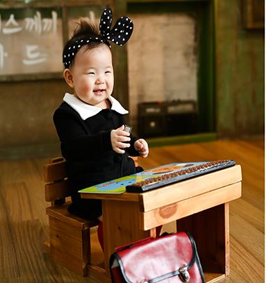 물방을 무늬 리본 머리띠를 하고 교복을 입은 여자아이가 책상이 앞에 놓인 의자에 앉아 있다