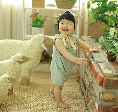 하늘색 옷을 입은 여자 아이가 탁자를 집고 서서 옆으로 돌아보면서 웃고 있다