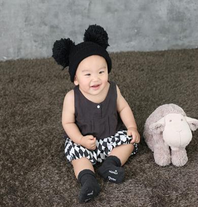 미키마우스 모자를 쓰고 진회색 조끼와 흰무늬 바지를 입은 남자아이가 앉아서 웃고 있다.