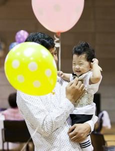 분홍색, 노란색 풍선을 든 삼촌 품에 안겨있는 유빈이